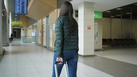 Traveler woman is walking in modern airport terminal carrying suitcase, back view. Traveler woman brunette is walking in modern airport terminal carrying stock video footage