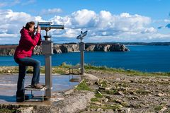 Traveler woman watching through the stationary binoculars. At a scenic overlook in Brittany, France Royalty Free Stock Images