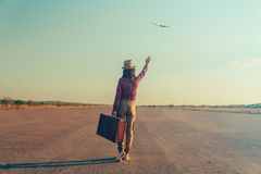 Traveler woman waves her hand to airplane Royalty Free Stock Photography
