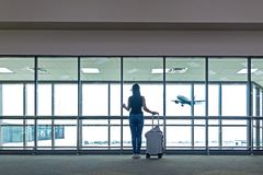 Traveler women plan and backpack see the airplane at the airport glass window, Asian tourist hold bag and waiting near luggage in. Hall airplane departure stock image