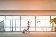 Traveler women plan and backpack see the airplane at the airport glass window, girl tourist hold bag and waiting near luggage in h royalty free stock image