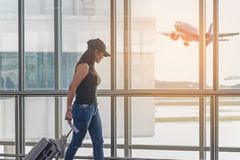 Traveler women plan and backpack see the airplane at the airport glass window, girl tourist hold bag and waiting near luggage in h. Traveler woman plan and royalty free stock photography