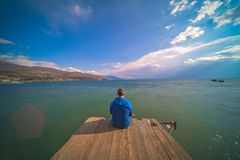 Traveler on a wooden pier admiring Ohrid Lake. Male traveller sitting on a wooden pier and admiring the beauty of Ohrid Lake, Northern Macedonia royalty free stock image
