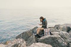 Traveler working on digital tablet on coast Stock Images