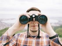 Traveler young man looking through binoculars outdoor. royalty free stock image