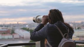 Young woman tourist with backpack looking at city through coin-operated binoculars during sunset time in slow motion. Traveler young woman tourist looking at stock footage