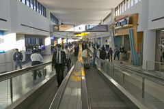 Travelers and airline industry personnel on moving sidewalks in Newark International Airport, New Jersey Stock Photos