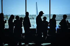 Travelers at Airport. Travelers standing in line at the airport waiting to board an airplane stock image