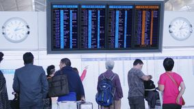 Travelers in airport. Passengers in front of airport information board in Hong Kong International Airport stock footage