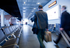 Business travel. People carrying luggage to departure gate preparing to travel by plane Stock Image