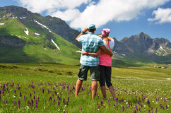Travelers in an Alpine meadow Royalty Free Stock Images