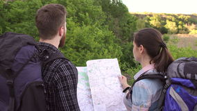 Travelers with backpacks looking at map, close-up. Group of young tourists are standing in the forest and look at the map. Travelers with backpacks looking at stock video footage