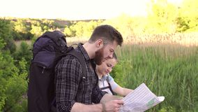 Travelers with backpacks looking at map, close-up. Young couple of tourists looking at map in search of attractions in the background of big mountains stock video