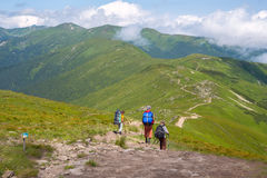 Travelers with backpacks are walking down the ridge. Among green slopes and clouds. Interesting and difficult adventure. Back view Royalty Free Stock Photography