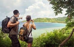 Travelers with backpacks watching through binoculars enjoying vi Royalty Free Stock Photos
