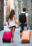 Travelers with baggage in the street. Tourist couple with baggage heading to hotel on foot Royalty Free Stock Photo