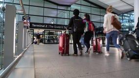 Travelers baggage walking modern airport terminal London UK. Business trip travelers Heathrow Airport Queen`s Terminal July 2017 stock video