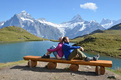 Travelers on a bench enjoying Alpine panorama Stock Photo