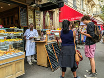 Travelers choose snacks from storefront restaurant in Paris, France. Tourists or travelers select snacks from menu outside restaurant in Paris, France Stock Images
