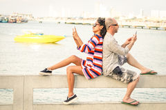Travelers couple in disinterest moment with mobile phones. At Pattaya beach - Apathy and addiction concept with bored people using smartphones Stock Photography