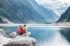 Travelers couple look at the mountain lake. Adventure and travel in the mountains region in the Austria. Travelers couple look at the mountain lake. Travel and royalty free stock photos