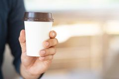 Travelers drink hot coffee before traveling. To want the body refreshed. Business man hand holding paper cup of take away drinking coffee on natural morning royalty free stock photo