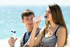 Travelers drinking cold water on the beach Stock Photography