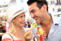 Travelers eating fresh fruits. Couple of tourists having fun eating fresh fruits stock photo