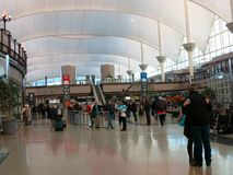 Travelers Embrace in Denver Airport (DIA) Lobby Stock Image