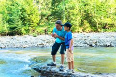 Travelers - father and son are standing on the shore of mountain. River, keenly watching the streams of water and small waterfalls on a wonderful sunny evening Stock Photos
