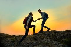 Travelers Hiking in the Mountains at Sunset. Man Helping Woman to Climb to the Top. Family Travel and Adventure. stock photos