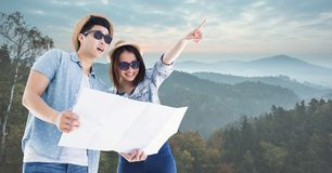 Travelers holding map on mountain Stock Photo
