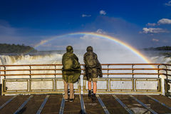 Travelers at Iguazu Falls. View of the rainbow and a waterfall. Royalty Free Stock Image