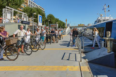 Travelers leaving the water bus moored at Willemskade. Royalty Free Stock Photography