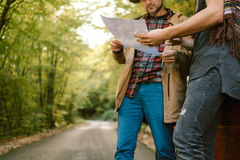 Travelers   looking map near car in autumn forest Royalty Free Stock Photography