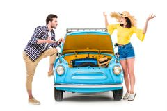 Travelers with luggage standing by car. Cheerful young travelers with luggage standing by car with open bonnet isolated on white Stock Images