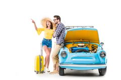 Travelers with luggage standing by car. Cheerful young travelers with luggage standing by car with open bonnet and pointing on something isolated on white Stock Images