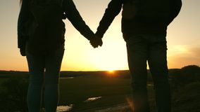 Travelers man and woman hold each other`s hands and enjoy the scenery at sunset. Lovers travelers travel with backpacks stock footage