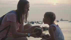 Travelers mother and daughter sits at seafront and drinks coconats in trip. Travelers mother and little daughter sits at seafront and drinks coconats in trip stock video footage