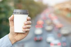 Travelers must drink hot coffee every time. Before driving. People man hand holding paper cup of take away drinking coffee on natural morning sunlight. space stock image