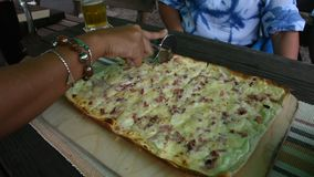 Travelers people cutting pizza thin crust for eat at restaurant. In Baden-Württemberg, Germany stock video