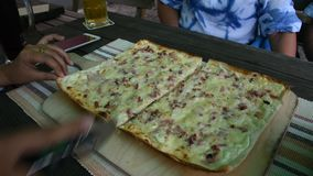 Travelers people cutting pizza thin crust for eat at restaurant. In Baden-Württemberg, Germany stock video footage