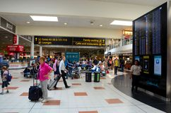 Travelers and people at England's London Gatwick Airport departure lounge with flight display. London Gatwick airport, England - June 24, 2014: Passengers and Royalty Free Stock Image