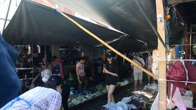 Travelers people visit and looking Mae klong Railway Market or Talat Rom Hup meaning the umbrella pulldown market. SAMUT SONGKHRAM, THAILAND - APRIL 12 stock footage