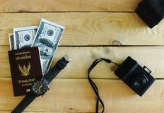 Prepare passports, banknotes, wrist watches, compact cameras on the desk royalty free stock photo