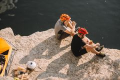 travelers in protective helmets eating canned food near tent logs axe and cauldron on rocky cliff over royalty free stock photography