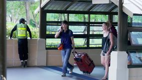 Thailand, Koh Samui, 19 january 2016. Travelers pulling suitcase from airport terminal arrived on Koh Samui. Vacation. Travelers pulling suitcase from airport stock video footage