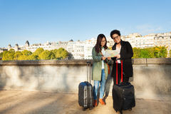 Travelers reading map at the embankment of Seine Stock Image
