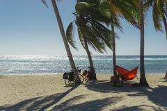 Playa giron, Cuba – January 2, 2017: Travelers relaxing on hammocks with bikes on tropical beach in Cuba, travel concept Royalty Free Stock Photo