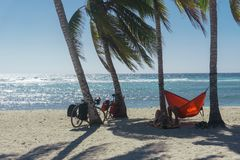 Playa giron, Cuba – January 2, 2017: Travelers relaxing on hammocks with bikes on tropical beach in Cuba, travel concept Stock Images